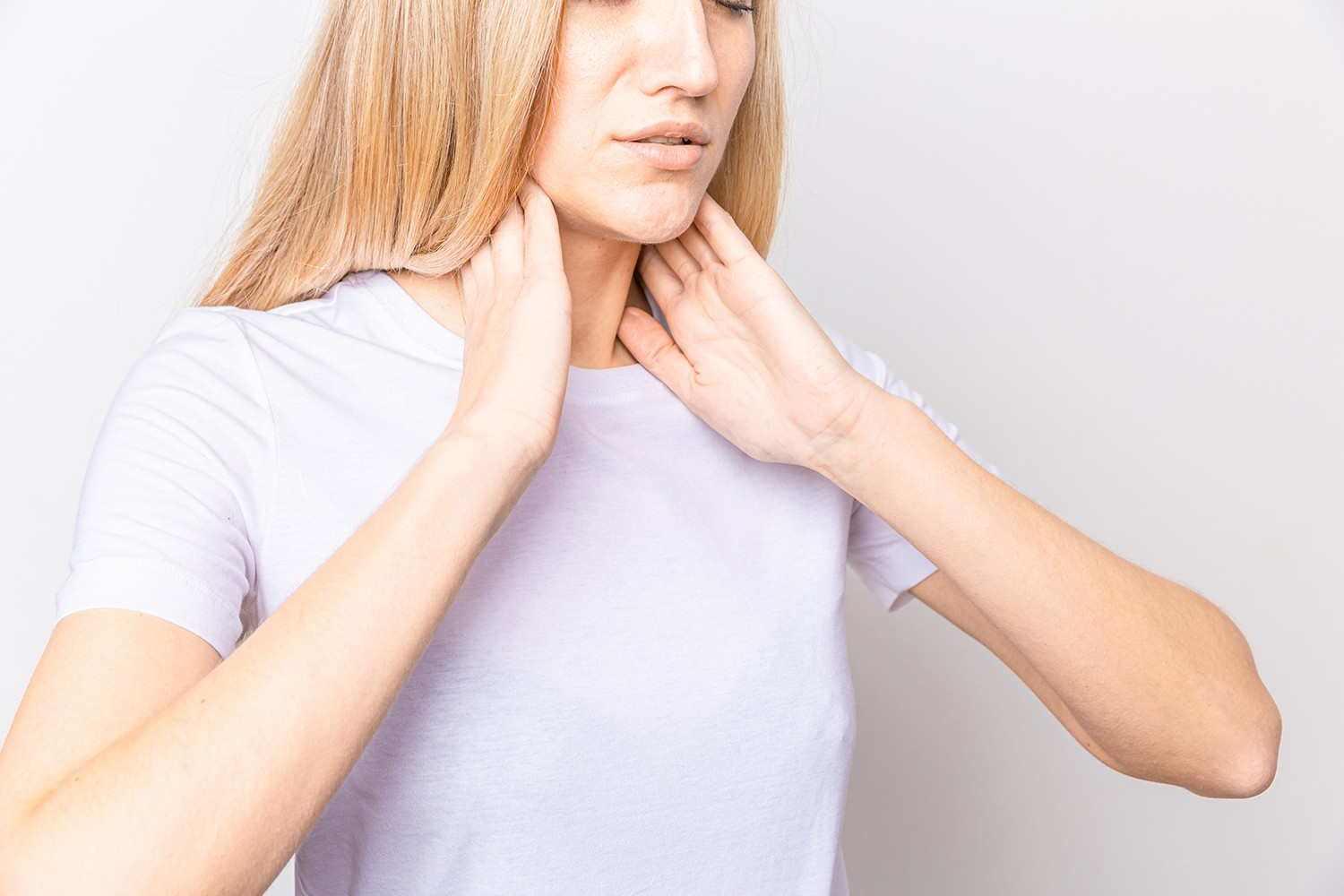 female checking thyroid gland by herself close up woman white t shirt touching neck with red spot thyroid disorder includes goiter hyperthyroid hypothyroid tumor cancer health care