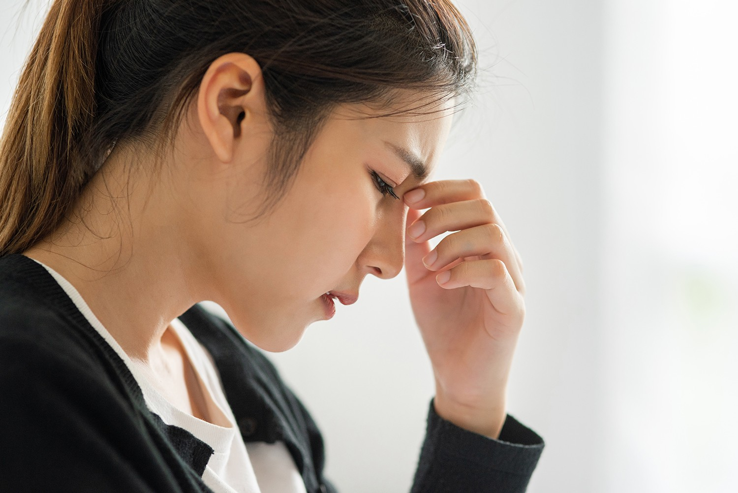sick woman had headache put her hand her nose bed
