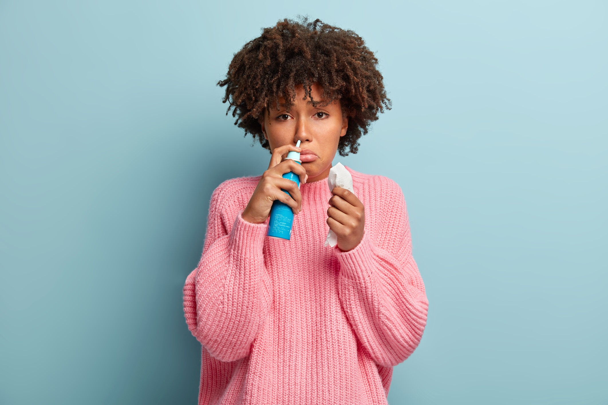 rsz portrait displeased afro american woman sniffs nasal aerosol feels sick has running nose uses medication blocked nose holds tissue has sad facial expression wears pink jumper
